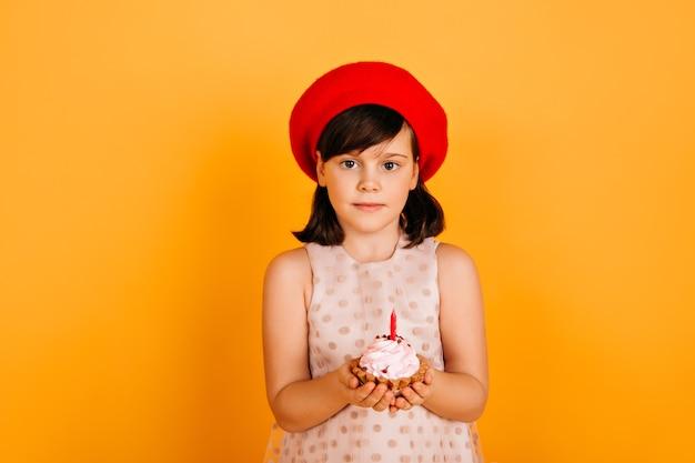 Joyeux Enfant En Béret Français Célébrant Son Anniversaire. Fille Préadolescente Extatique Avec Gâteau Isolé Sur Mur Jaune. Photo gratuit
