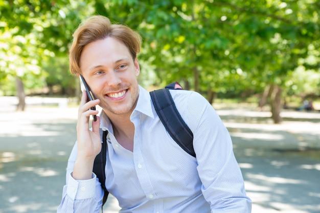 Joyeux étudiant heureux avec sac à dos, bavardant sur téléphone Photo gratuit
