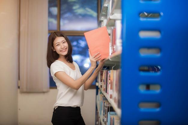 Joyeux étudiants universitaires heureux de lire un livre et de rédiger un rapport à la bibliothèque Photo Premium