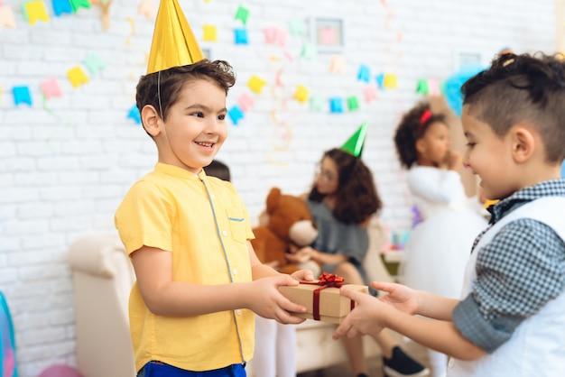 Joyeux garçon au chapeau d'anniversaire donne un cadeau au garçon d'anniversaire. Photo Premium