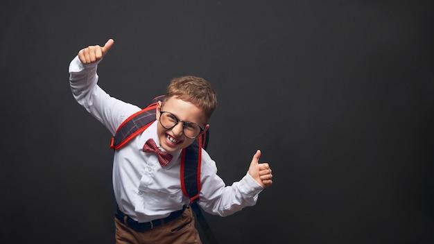 Joyeux Garçon Sur Fond Noir Avec Une Mallette Derrière Les épaules Photo Premium