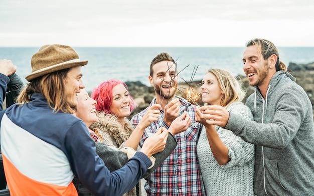 Joyeux Groupe D'amis Célébrant Avec Des Feux D'artifice D'étoiles Scintillantes En Plein Air Photo Premium