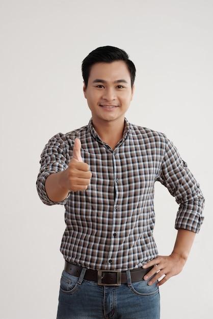 Joyeux homme asiatique en chemise à carreaux et jeans, debout dans le studio avec son pouce vers le haut Photo gratuit