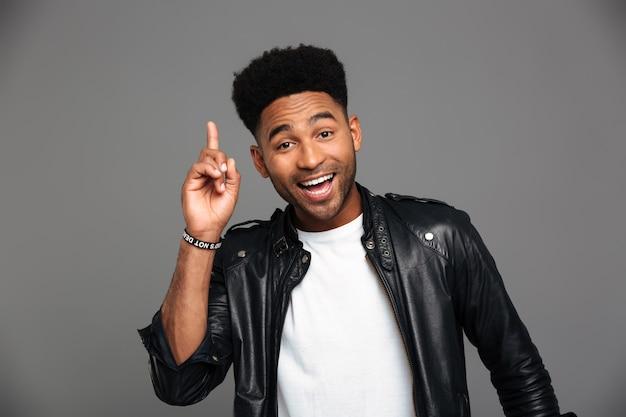 Joyeux Homme élégant Afro Américain Pointant Avec Le Doigt Vers Le Haut, à La Recherche Photo gratuit