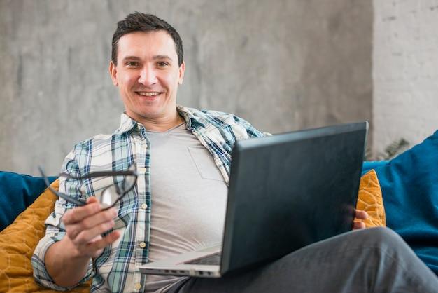 Joyeux homme travaillant sur un ordinateur portable à la maison Photo gratuit
