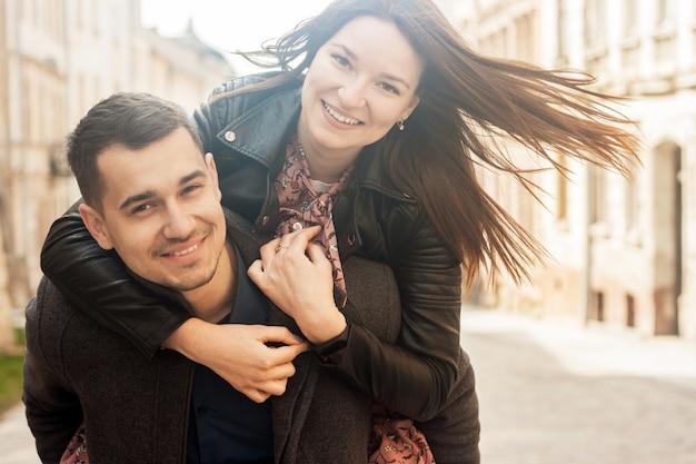 Joyeux jeune couple embrassant à la rue en journée ensoleillée Photo Premium