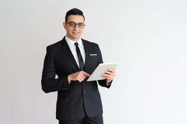 Joyeux jeune homme d'affaires vérifiant l'email sur la tablette et regardant la caméra. Photo gratuit