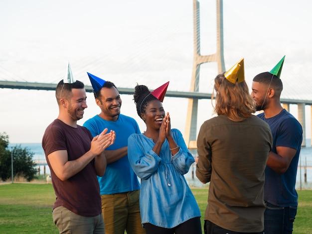 Joyeux jeunes faisant la surprise pour leur ami. bons amis offrant un cadeau pour une jeune femme heureuse. concept de surprise d'anniversaire Photo gratuit