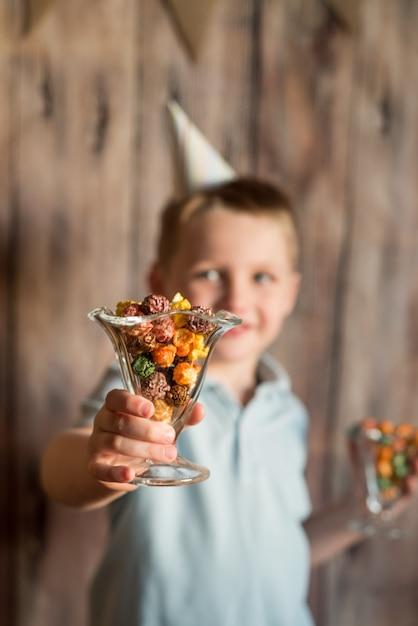 Joyeux joyeux petit garçon qui rit lors d'une fête. peut contenir un pop-corn coloré dans un verre. Photo Premium