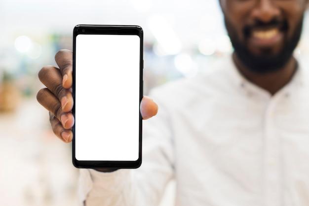 Joyeux Mâle Noir Adulte Montrant Un Téléphone Portable Sur Un Arrière-plan Flou Photo Premium