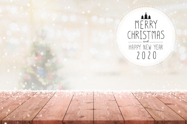 Joyeux noël et bonne année 2020 sur le dessus de table en bois vide sur fond d'arbre de noël flou bokeh avec des chutes de neige. Photo Premium