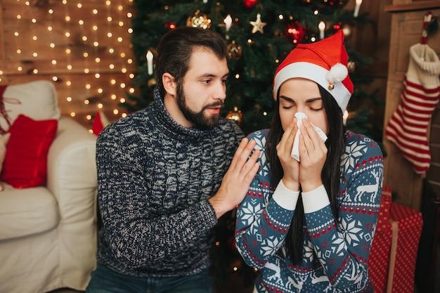 Joyeux Noel Et Bonne Année . Jeune Couple Fête à La Maison. Jeune Femme Avec Un Mouchoir. Malade A Le Nez Qui Coule Photo Premium