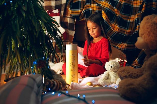 Joyeux Noël Et Bonnes Fêtes. Mignonne Petite Fille Enfant écrit La Lettre Au Père Noël Près De L'arbre De Noël à La Maison à L'intérieur. Vacances, Enfance, Hiver, Concept De Célébration Photo gratuit