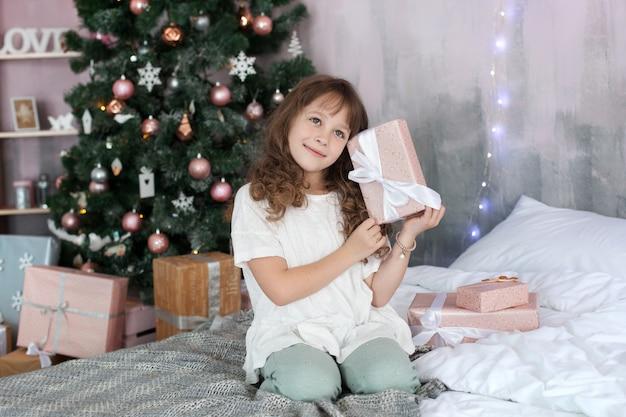 Joyeux Noël Et Bonnes Fêtes! Nouvel An 2020! Enfants, Famille Et Enfance Et Concept De Vacances. Fille En Pyjama Détient Un Cadeau Du Nouvel An Sur Le Fond D'un Arbre Du Nouvel An. Intérieur De Noël. Photo Premium