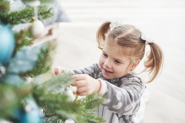 Joyeux noël et joyeuses fêtes! jeune fille aidant à décorer le sapin de noël, tenant des boules de noël à la main Photo Premium