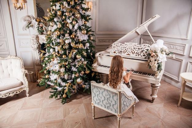 Joyeux Noël Et Joyeuses Fêtes. Jolie Petite Fille En Intérieur Classique Blanc Jouant Sur Un Piano Blanc Décoré De Sapin De Noël. Nouvel An Photo Premium