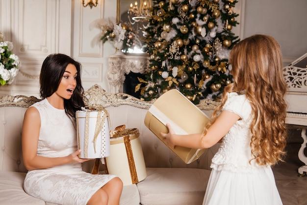 Joyeux Noël Et Joyeuses Fêtes. Joyeuse Maman Et Sa Fille Fille Mignonne échangeant Des Cadeaux En Piano Intérieur Classique Blanc Et Un Arbre De Noël Décoré. Nouvel An Photo Premium