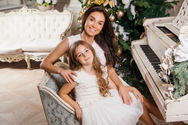 Joyeux Noël Et Joyeuses Fêtes. Joyeuse Maman Et Sa Fille Fille Mignonne En Piano Blanc Intérieur Classique Blanc Et Un Arbre De Noël Décoré. Nouvel An Photo Premium