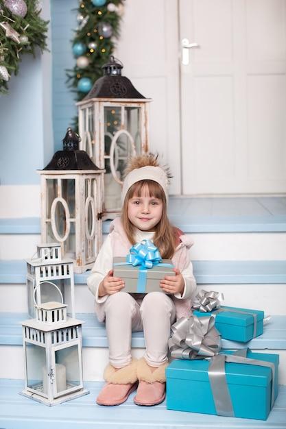 Joyeux Noël, Joyeuses Fêtes! Nouvel An 2020. Petite Fille Assise Avec Des Cadeaux Sur Le Porche D'une Maison Décorée Pour Noël. L'enfant Est Assis Sur La Véranda Décorée Pour Le Nouvel An. Enfant Ouvre Le Cadeau De Noël. Photo Premium