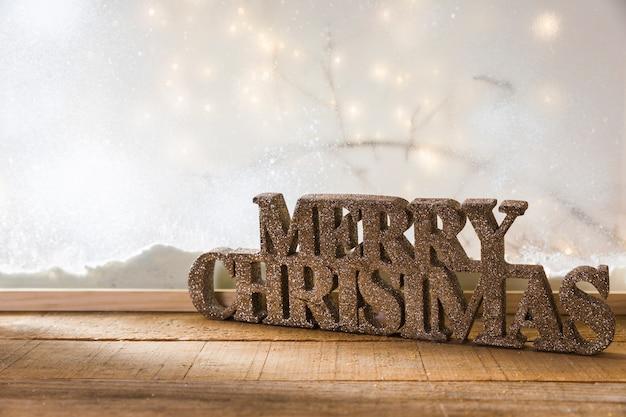 Joyeux noël signe sur la table en bois près de la berge de la neige et des guirlandes Photo gratuit