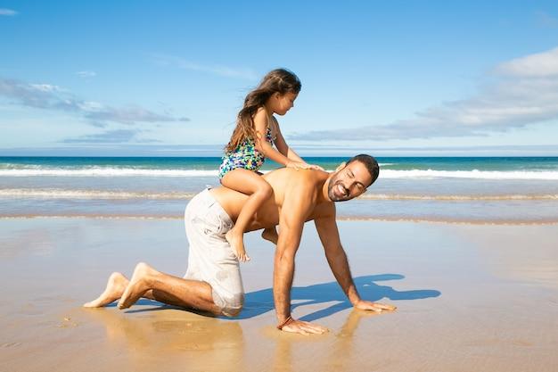 Joyeux Papa Va Sur Les Mains Et Les Genoux Sur La Plage, Portant Petite Fille Sur Son Dos Photo gratuit