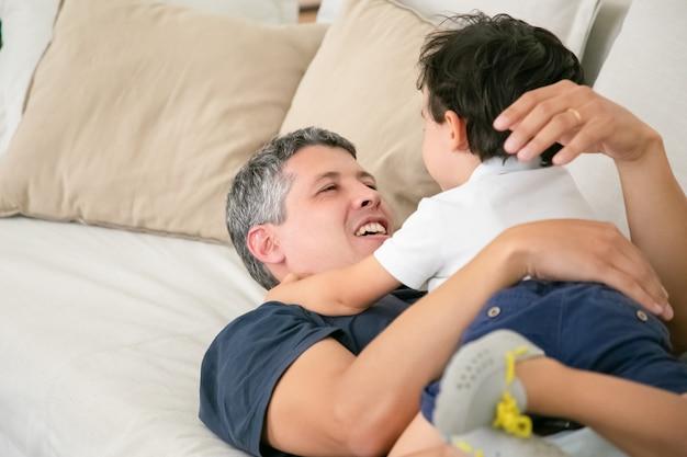 Joyeux Père Allongé Sur Le Canapé Avec Un Adorable Petit Garçon. Photo gratuit