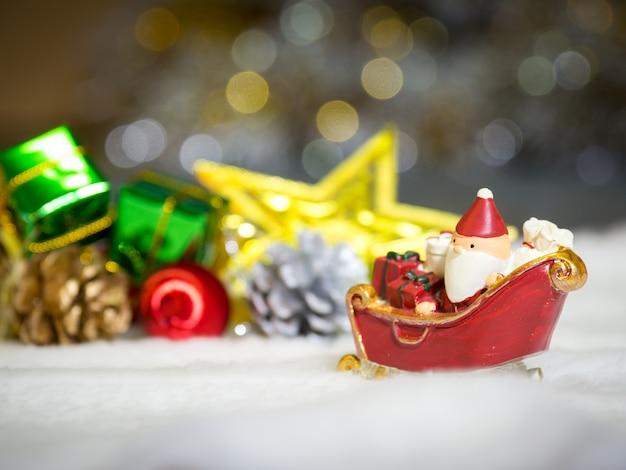 Joyeux Père Noël Avec Boîte-cadeau Sur Le Traîneau à Neige Est Le Décor De Noël. Photo Premium