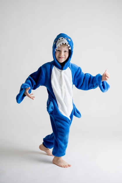 Joyeux petit garçon posant sur fond blanc en pyjama, costume de requin bleu Photo Premium