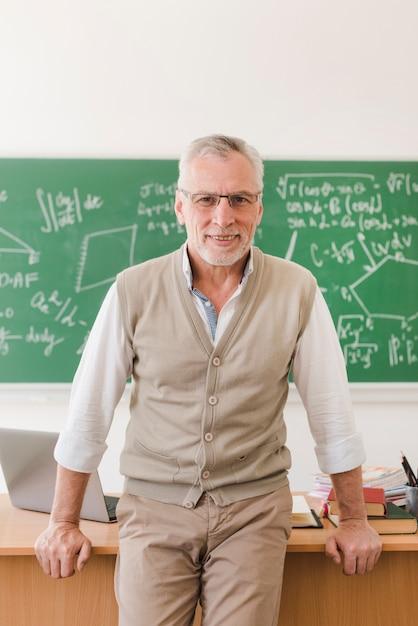 Joyeux professeur senior debout près du bureau de l'enseignant dans la salle de lecture Photo gratuit