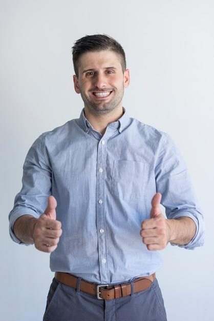 Joyeux succès bel homme d'affaires avec chaume montrant le pouce en l'air Photo gratuit
