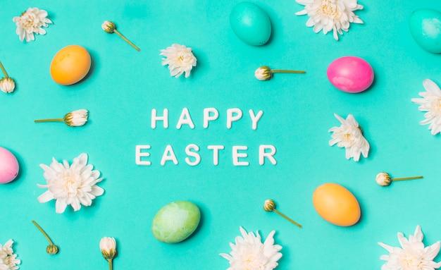 Joyeux titre de pâques entre les œufs et les boutons floraux Photo gratuit