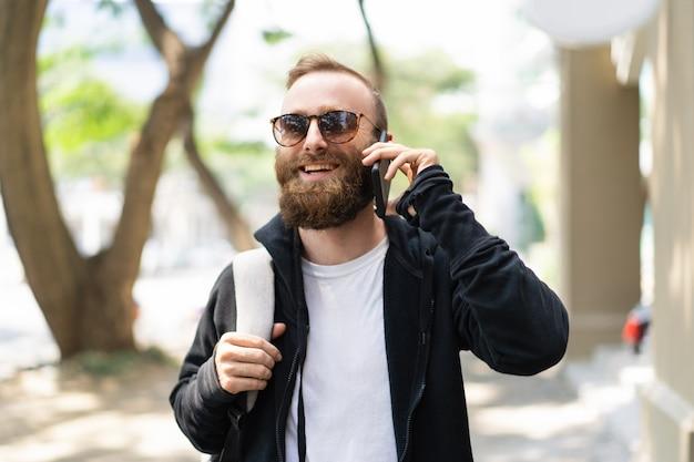 Joyeux touriste bénéficiant d'un appel international Photo gratuit
