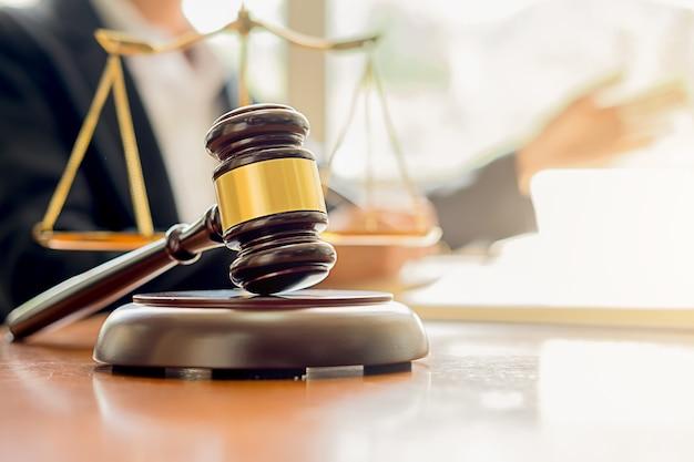 Juge marteau avec les avocats de la justice ayant une réunion d'équipe à l'arrière-plan de la firme d'avocats. Photo Premium