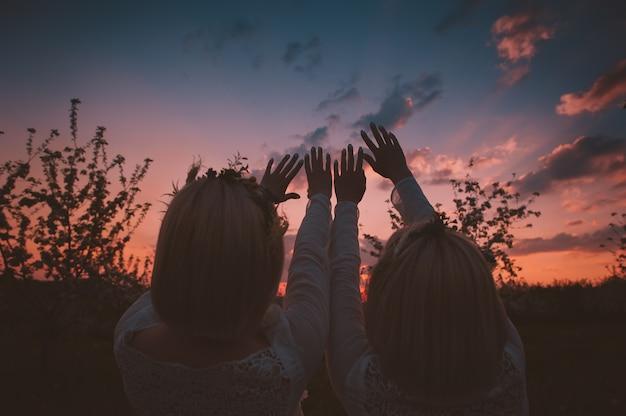 Jumeaux s'étirant les mains vers le ciel Photo Premium