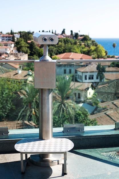 Jumelles sur une plate-forme d'observation avec vue sur la mer et les toits de tuiles rouges Photo Premium