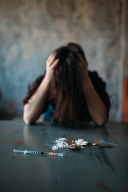Junkie Assis à La Table Avec Des Médicaments Et Une Seringue Photo Premium