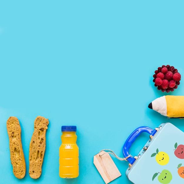 Jus et des aliments sains près de lunchbox et étui à crayons Photo gratuit