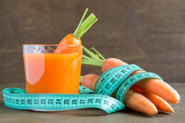 Jus de carottes mûres fraîches sur un fond marron. Photo Premium