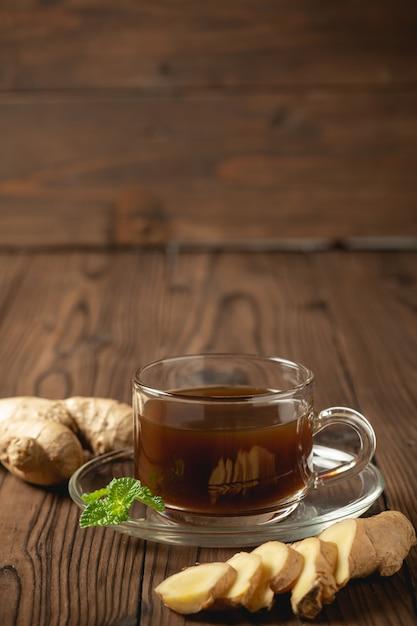 Jus de gingembre chaud et gingembre tranchés sur une table en bois. Photo gratuit