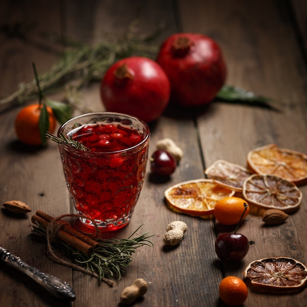 Jus de grenade avec des grenades et des fruits secs sur une table en bois. style campagnard. Photo Premium