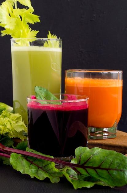 Jus de légumes dans des tasses en verre sur fond noir. betteraves, céleri, carottes. Photo Premium