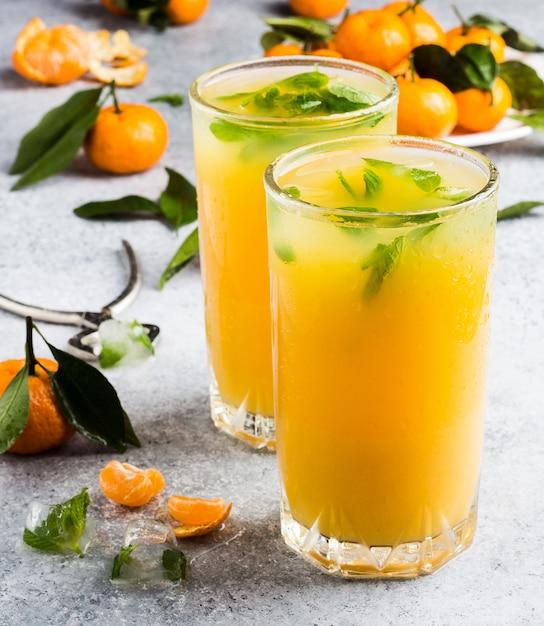 Jus de mandarine dans des verres à la lumière Photo gratuit