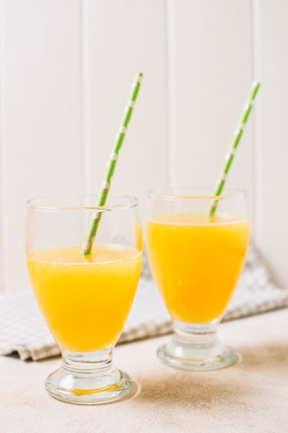 Jus d'orange frais avec des pailles Photo gratuit