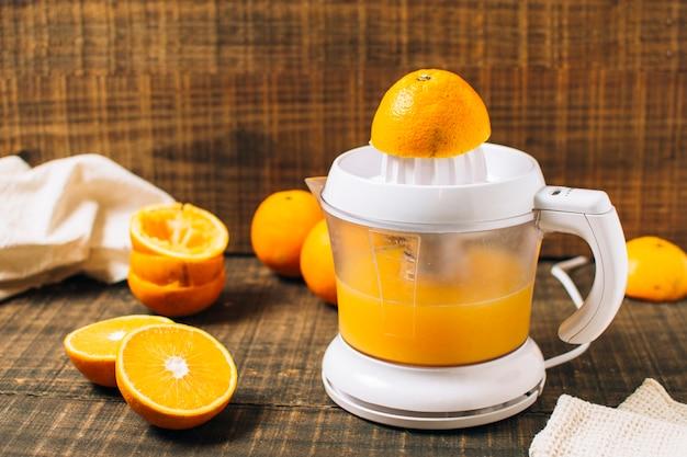 Jus d'orange frais avec presse-agrumes manuel Photo gratuit