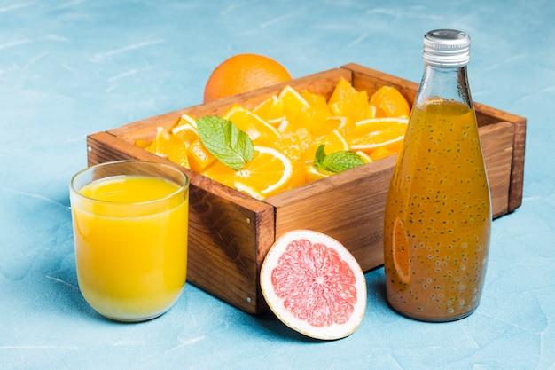 Jus d'orange et fruits dans une boîte en bois Photo gratuit