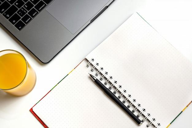 Jus d'orange sur le lieu de travail. ordinateur portable, verre de jus d'orange et cahier sur le bureau blanc. Photo Premium