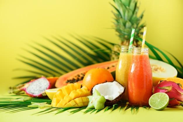 Jus de papaye et d'ananas juteux, mangue, smoothie aux fruits d'orange dans deux pots. detox, régime alimentaire d'été, concept végétalien. Photo Premium