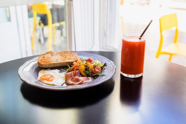 Jus; petit déjeuner frais sur une plaque grise au-dessus du tableau noir Photo gratuit