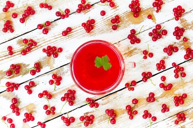 Jus rouge fraîchement pressé avec des feuilles de cassis et des grappes de groseilles sur une table en bois blanche avec des peintures anciennes. Photo Premium