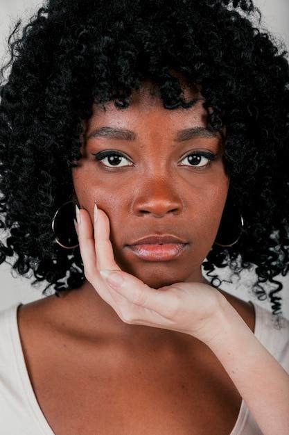 Juste main toucher le menton d'une femme africaine en regardant la caméra Photo gratuit
